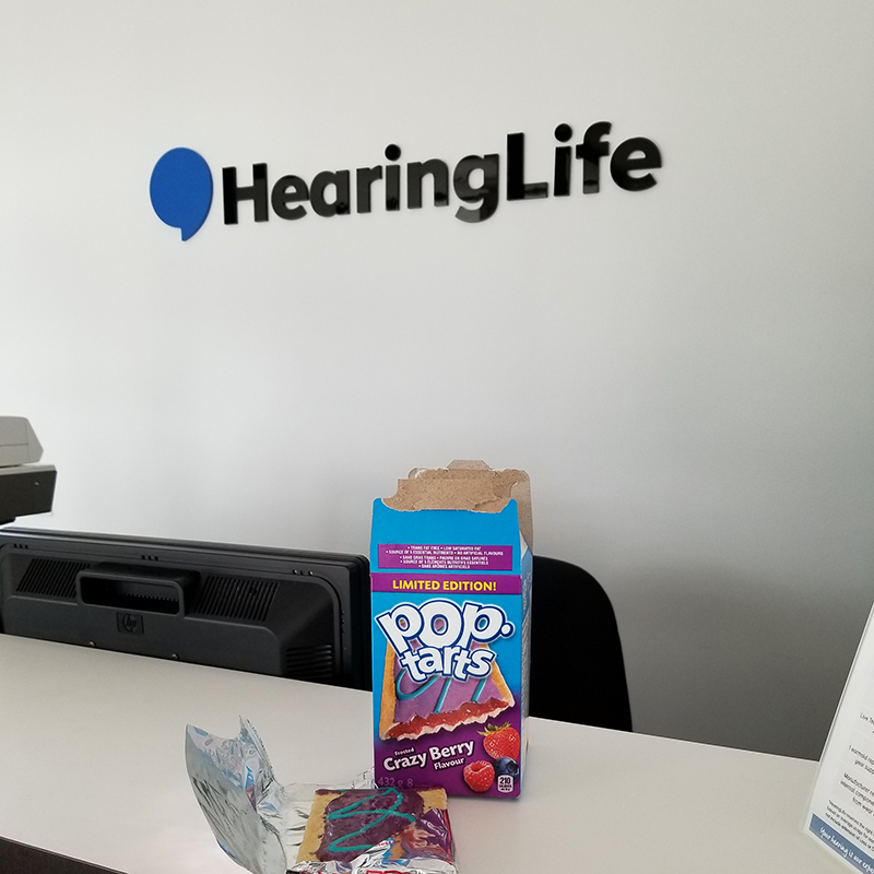 Pop Tarts on a reception desk in front of a HearingLife sign